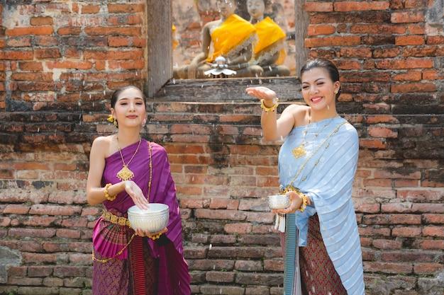 Thailändische mädchen im thailändischen trachtenkleidwasser während festival songkran-festivals, ayutthaya, thailand.