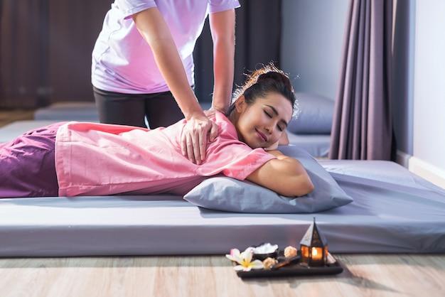 Thailändische massagetherapie auf bett zur jungen schönen asiatischen frau im spa-salon. gesundheitswesen und entspannung, um schmerz zu heilen konzept. alternative gesundheitsbranche.