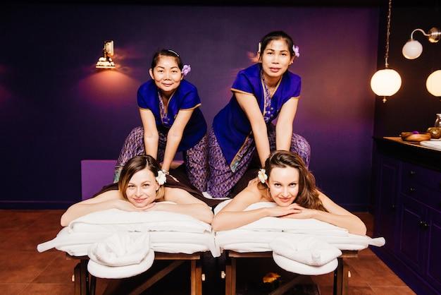 Thailändische masseure in ethnischer kleidung machen traditionelle kuranwendungen für schöne, glückliche frauen