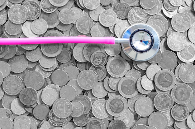 Thailändische münze des hintergrundgeschäftsgeschäftskonzeptes, stethoskop-gesundheitsfinanzgeldmünze auf weißem hintergrund
