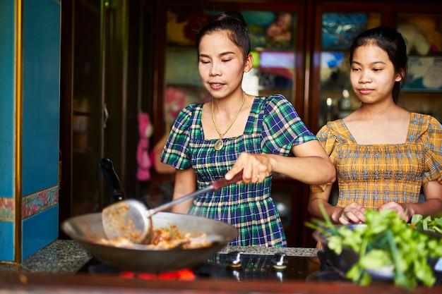Thailändische mutter kocht zusammen mit jugendlich tochter in der rustikalen küche