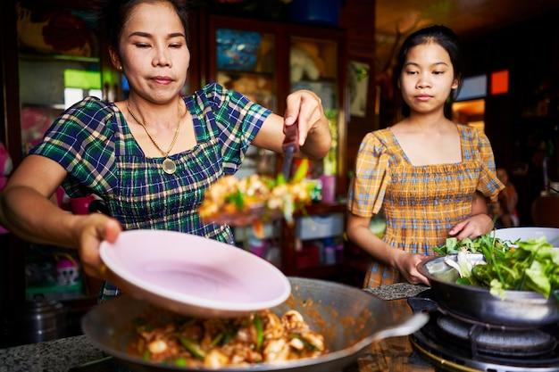Thailändische mutter und tochter, die frisch gekochtes rotes curry in der rustikalen traditionellen küche überziehen