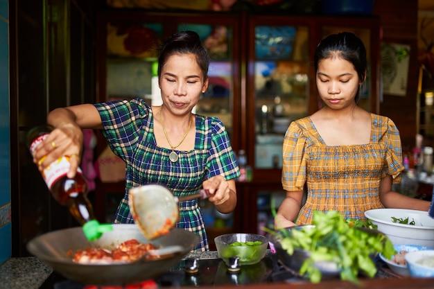 Thailändische mutter und tochter, die rotes curry zusammen in der traditionellen hauptküche kochen