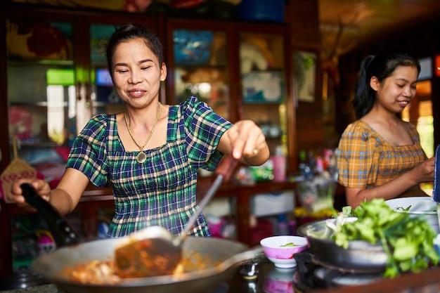Thailändische mutter und tochter kochen zusammen in der rustikalen küche, die rotes curry macht