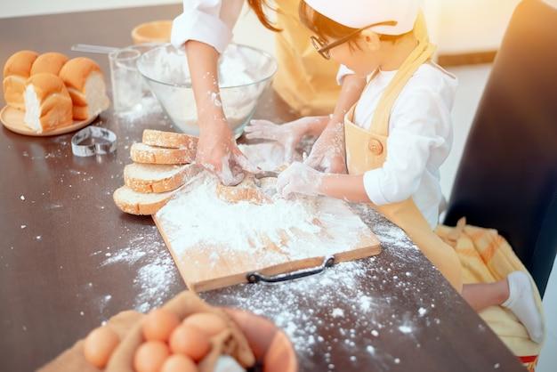 Thailändische mutter unterrichtet asiatisches kind für kochessen. zubereitung einer zutat mit mehl und brot.