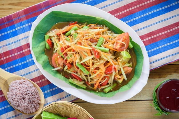 Thailändische nordöstliche küche genannt som tam oder scharfer grüner papayasalat mit beilagen