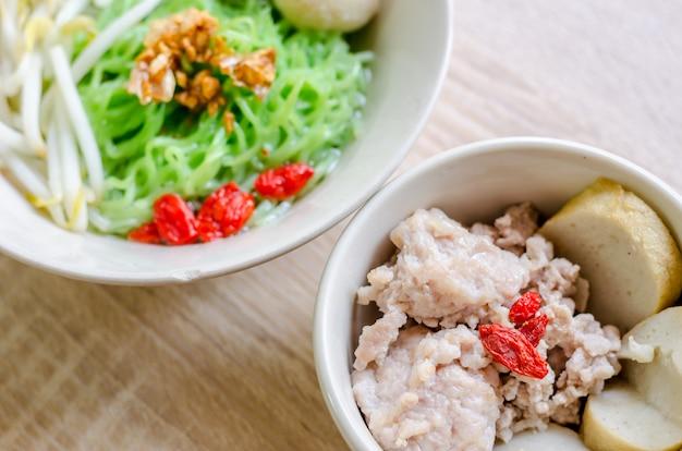 Thailändische nudel mit fischball und knusperiger schweinefleischhaut auf hölzernem hintergrund. thai essen