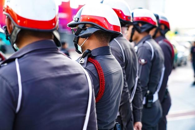 Thailändische polizisten tragen den helm, stehen in der reihe.