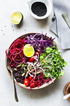 Thailändische reisbeere mit rote-bete-wurzeln, rosella-sprössling, tomate, kürbiskern-salatschüssel