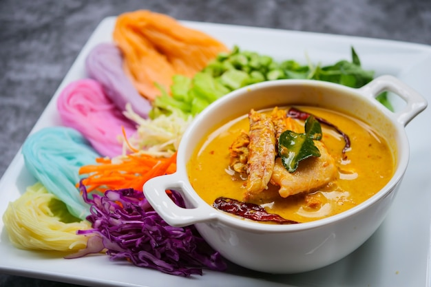 Thailändische reisnudeln in curry-sauce mit gemüse