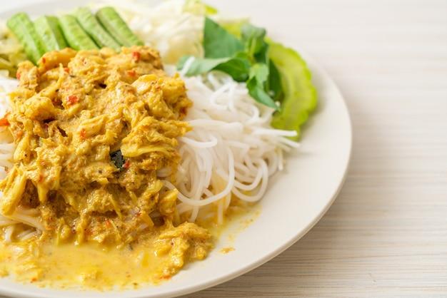 Thailändische reisnudeln mit krabbencurry und verschiedenen gemüsesorten