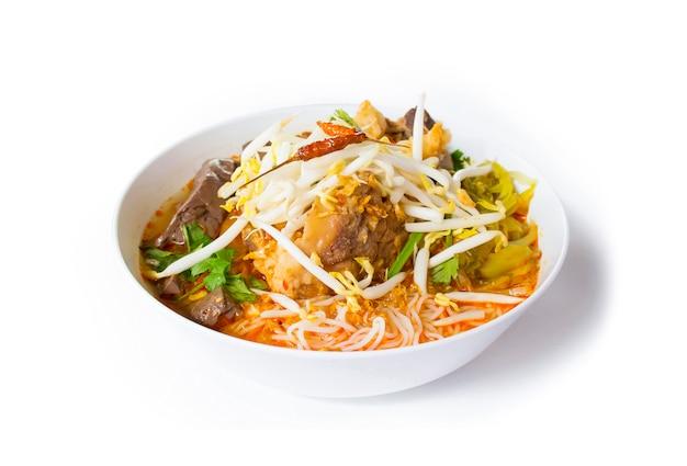 Thailändische reissuppennudeln mit würziger schweinefleischsoße. thailändisches nordlebensmittel gemacht von den reissuppennudeln oder von der reisnudel in der würzigen soße mit der seitenansicht des schweinefleischs oder des fleisches lokalisiert
