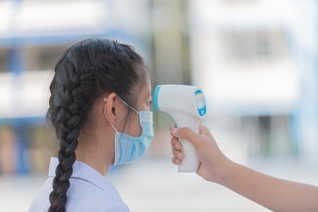 Thailändische schüler überprüfen ihre körpertemperatur, bevor sie zur schule gehen.