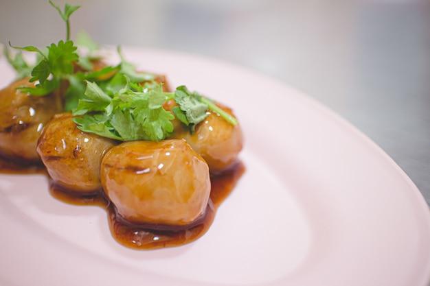 Thailändische schweinefleischbällchen mit brauner süßer soße auf plastikschale.
