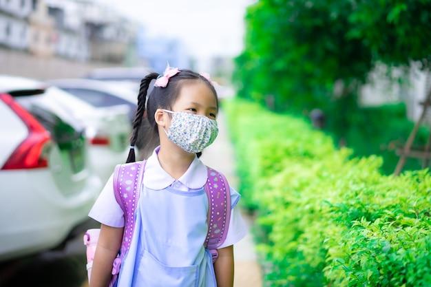 Thailändische studentin, die eine maske gegen coronavirus trägt, bevor sie zur schule geht