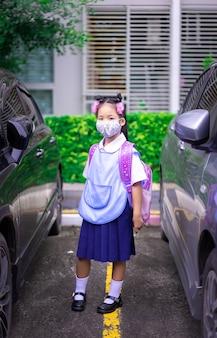 Thailändische studentin, die eine maske gegen coronavirus und pm 2.5 luftverschmutzung trägt, bevor sie zur schule geht