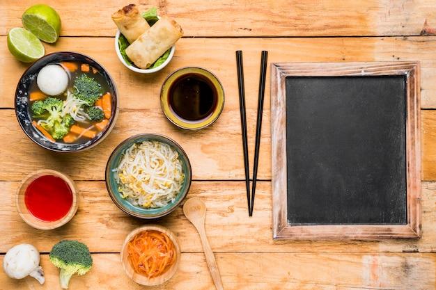 Thailändische suppe; frühlingsrollen; saucen und sprossenbohnen mit essstäbchen über dem holztisch