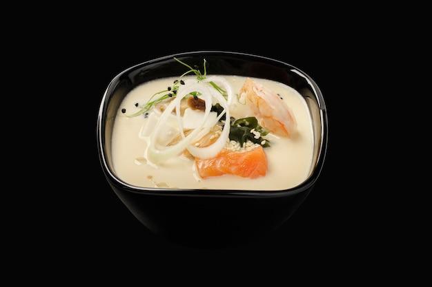 Thailändische suppe mit meeresfrüchten, lachs, tigergarnelen, muscheln, hondashi, shiitake-pilzen, togarashi-pfeffer, lauch, sesam