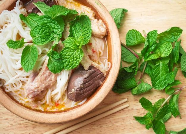 Thailändische suppennudeln gegessen mit curry und gemüse auf hölzerner schale