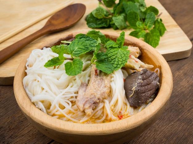 Thailändische suppennudeln gegessen mit curry und gemüse in der hölzernen schüssel