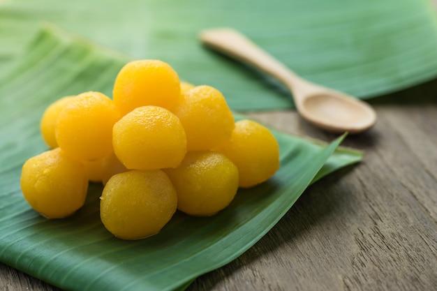 Thailändische traditionelle nachtisch-goldeigelb-tropfen auf den bananenblättern, hölzerne spitzentabelle