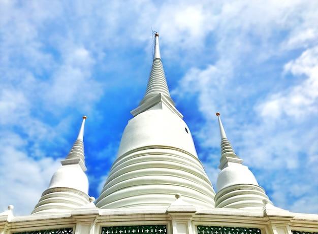 Thailändische weiße pagode mit blauem wolkenhimmel in einem thailändischen tempel