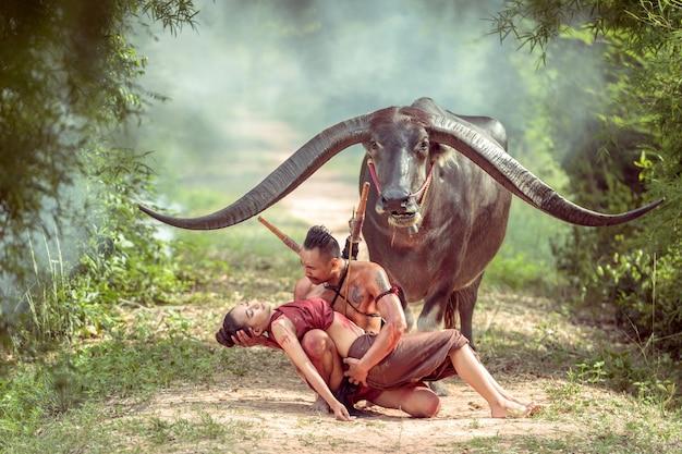 Thailändischer alter krieger, der eine zweihandklinge und einen langen hornbüffel hält