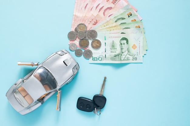 Thailändischer baht, banknoten und münzen mit automodell auf farbhintergrund