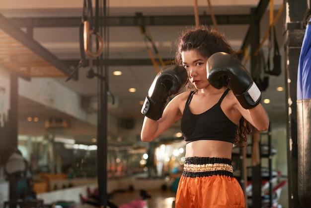 Thailändischer boxer muay, der die kamera bereit betrachtet, einen durchschlag zu geben