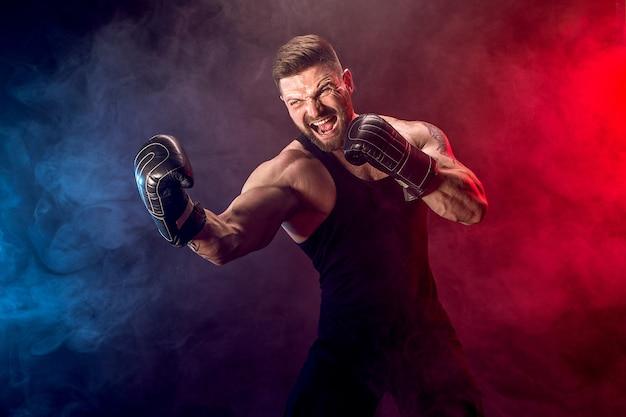 Thailändischer boxer sportlers muay, der auf schwarzer wand mit rauche kämpft.
