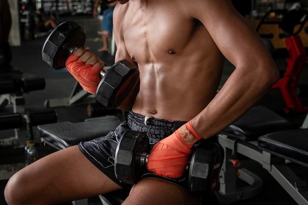 Thailändischer boxersportmann, der übung mit dummköpfen tut.