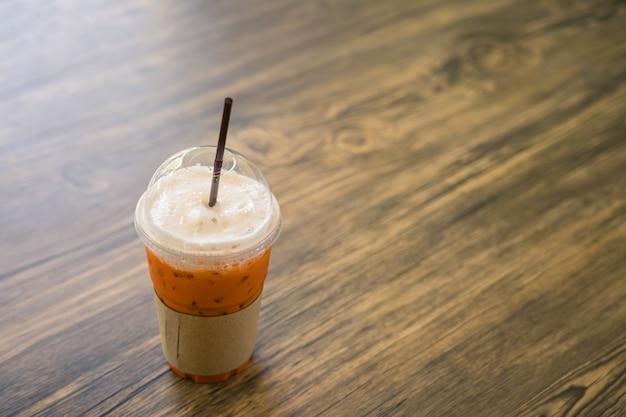 Thailändischer eistee auf hölzerner tabelle im café.