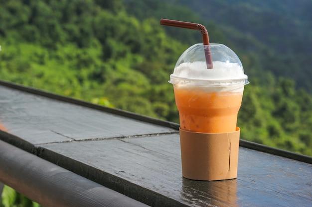 Thailändischer eistee in der plastikschale mit natual-ansicht als hintergrund.