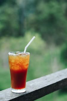 Thailändischer eistee mit lokalem getränk der kalkzitronenunterzeichnung auf teeplantagehintergrund