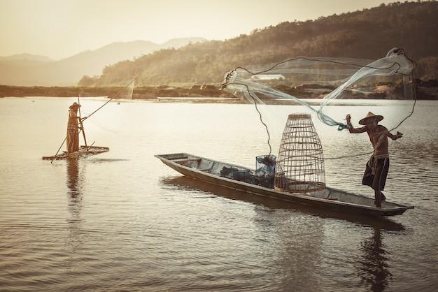 Thailändischer fischer auf dem hölzernen boot, das ein netz für anziehende frischwasserfische im naturfluß wirft