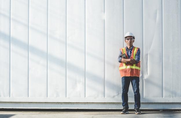Thailändischer gutaussehender manningenieur, der mit einem meter vor dem behälter steht.