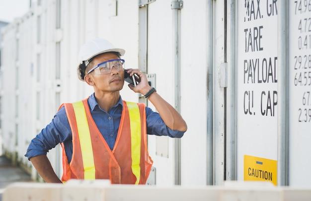 Thailändischer ingenieur des gutaussehenden mannes, der am telefon vor dem behälter steht.