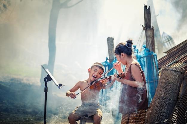 Thailändischer junge und ländliche mädchen, die violine an ihrem hausgarten spielen.