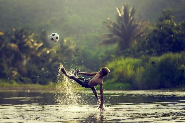 Thailändischer jungenspielfußball und tritt oben auf den sonnenuntergang.