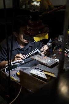 Thailändischer juwelier, der feinen schmuck in einer werkstatt macht