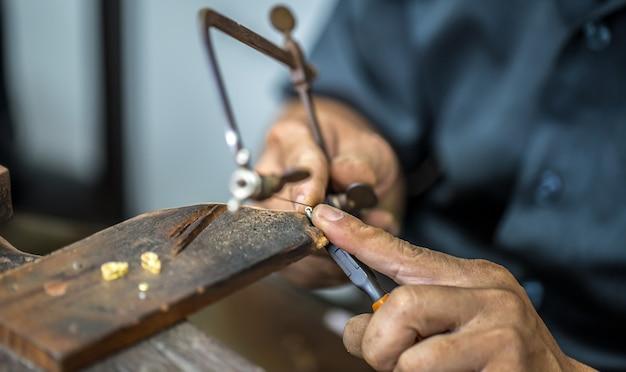 Thailändischer juwelier, kümmert sich um den schmuck und die edelsteine in der werkstatt, den prozess der schmuckherstellung, nahaufnahme