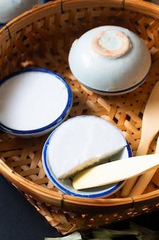 Thailändischer kokosnussreis kanom tuay und pandan-vanillepudding des lebensmittelnachtischkonzeptes in der kleinen porzellanschale