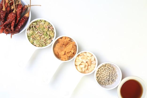 Thailändischer krauthintergrund mit getrockneten paprikas, pfeffer, zitronengras, knoblauch, kokosnusszucker und fischsauce
