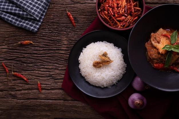 Thailändischer küchentisch mit getrocknetem rotem schweinefleischkokosnusscurry.