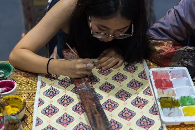 Thailändischer künstler, der thailändische kunst für die herstellung der thailändischen seide zeichnet