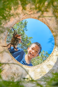 Thailändischer landwirtjunge krabben in den prahlern glücklich fangen