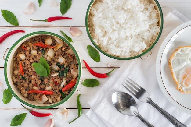 Thailändischer lebensmittelname pad ka prao, draufsichtbild von angebratenem schweinefleisch mit basilikumblättern haben dazu gekochten reis und spiegelei auf dem teller, der auf weiße hölzerne tabelle eingestellt wird