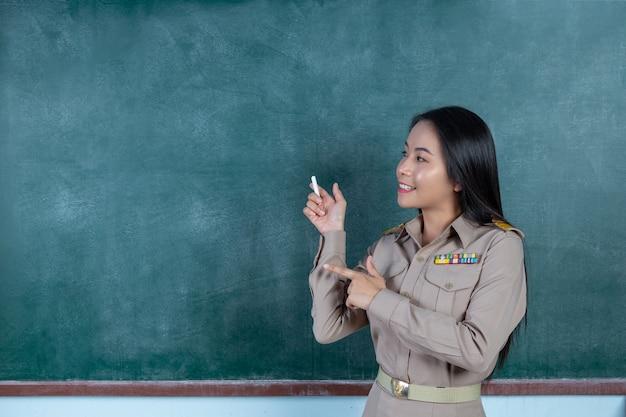 Thailändischer lehrer im offiziellen outfit, der vor dem rückenbrett unterrichtet
