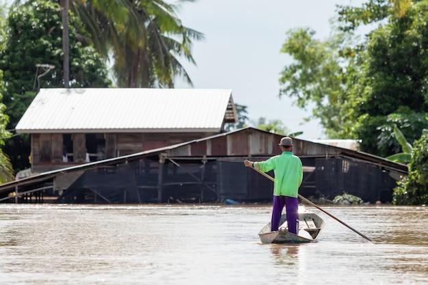 Thailändischer mann auf dem boot und schauen zu seinem haus
