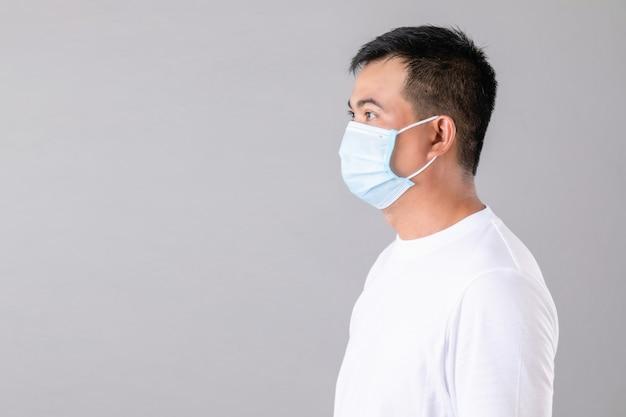 Thailändischer mann, der eine schützende gesichtsmaske trägt
